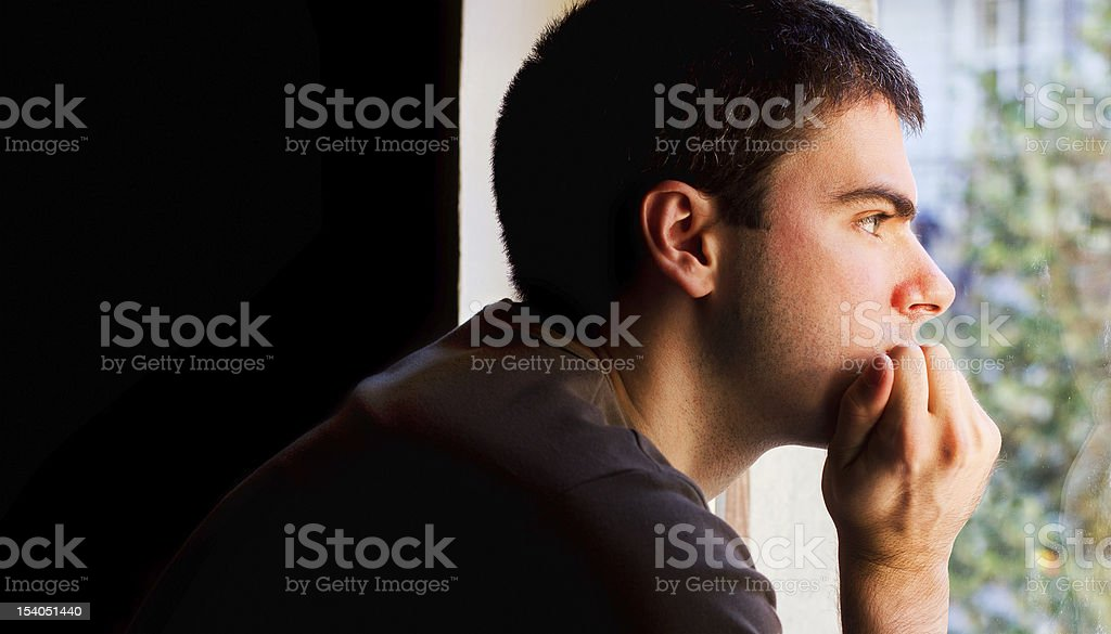 Sad man looking out the window royalty-free stock photo