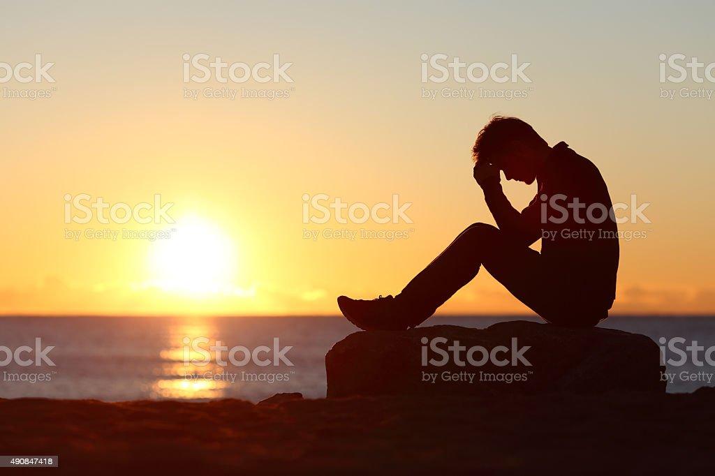Sad man silhouette worried on the beach stock photo