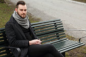 Sad man sitting down outdoors