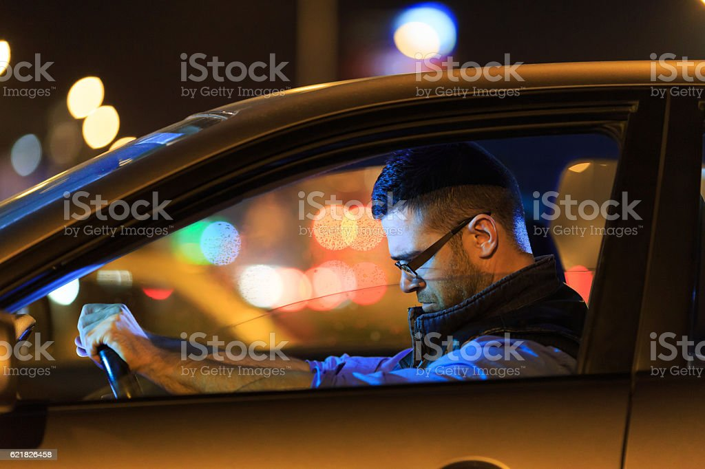 Sad man sitting in car at night stock photo