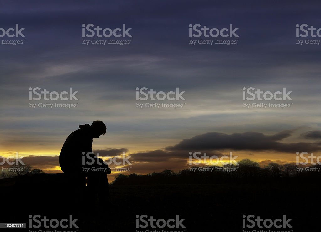Sad man sitting in sunset stock photo