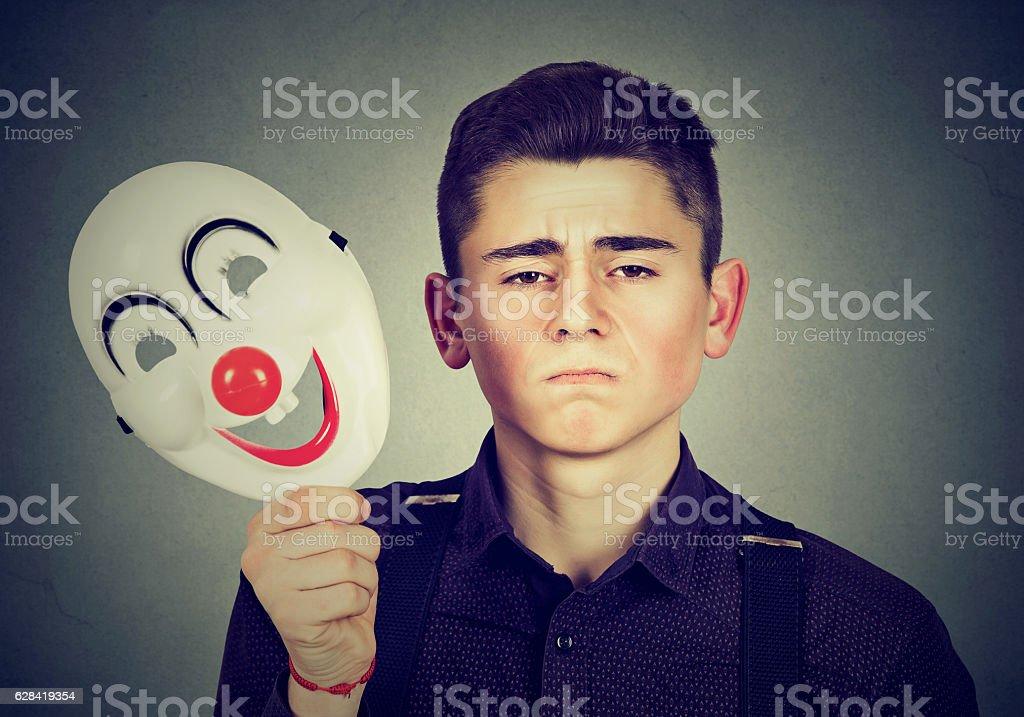Sad man taking off clown mask. Split personality stock photo