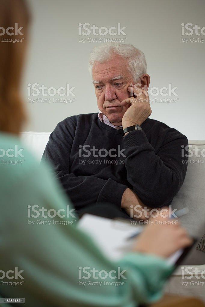 Sad man talking with psychiatrist stock photo