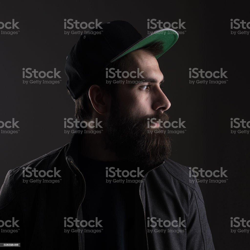 Sad man wearing baseball cap looking away stock photo