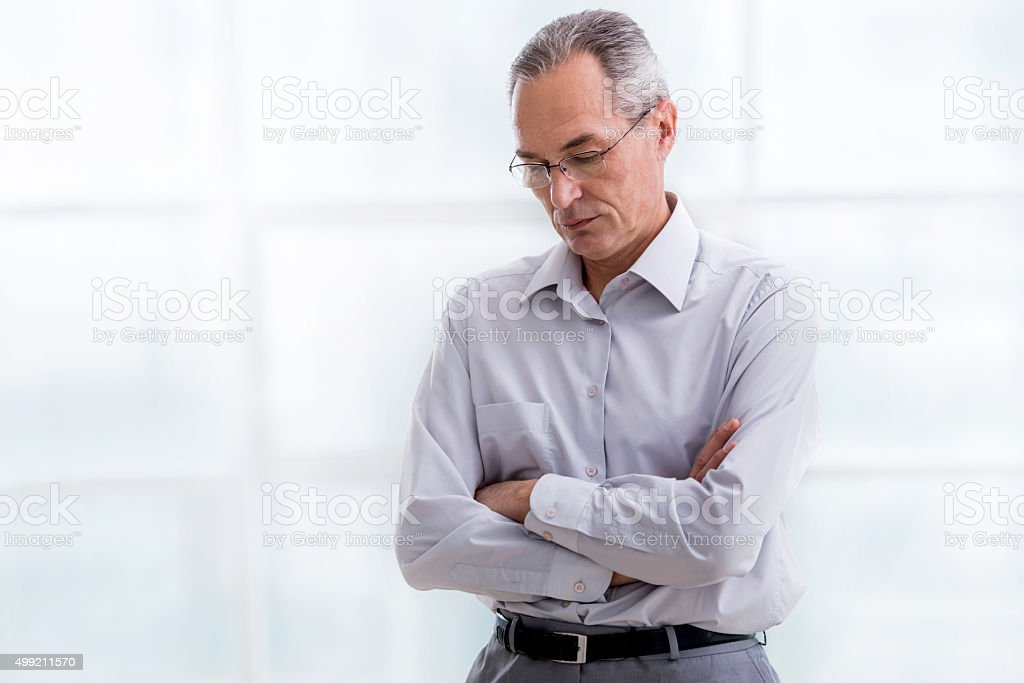 Sad mature businessman standing with his arms crossed. stock photo