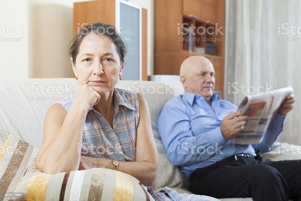 sad mature woman against elderly man with newspaper royalty-free stock photo