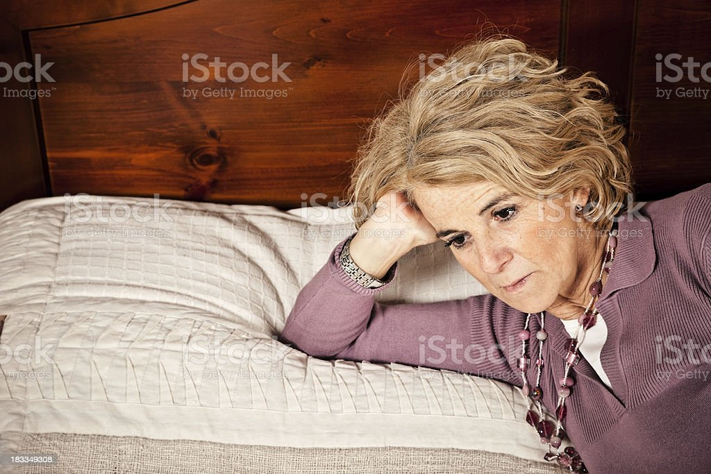 Sad Mature Woman Lying On The Bed royalty-free stock photo