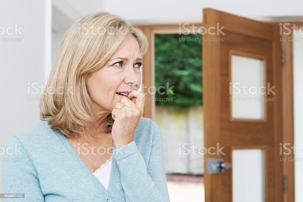 Sad Mature Woman Suffering From Agoraphobia Looking Out Of Open stock photo
