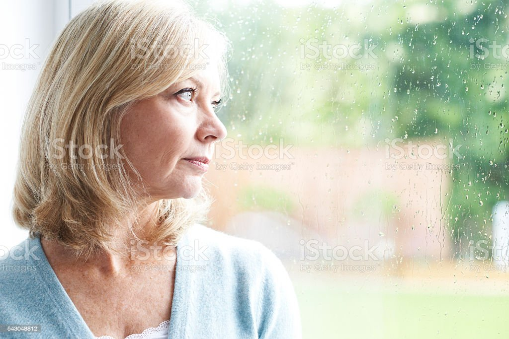 Sad Mature Woman Suffering From Agoraphobia Looking Out Of Windo stock photo