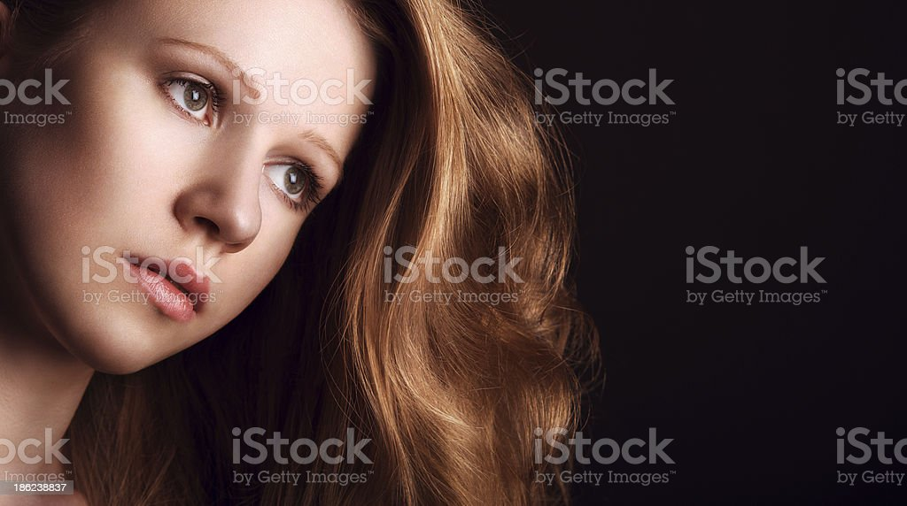 sad, melancholy girl with long red hair on dark background royalty-free stock photo