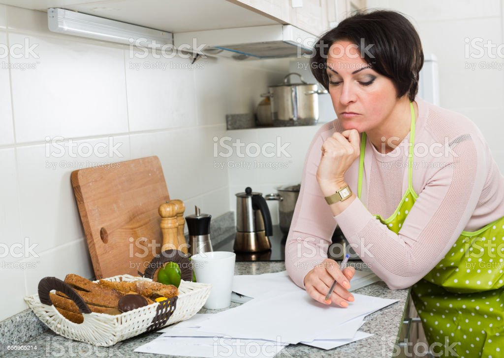 Sad middle aged housewife looking through bills stock photo