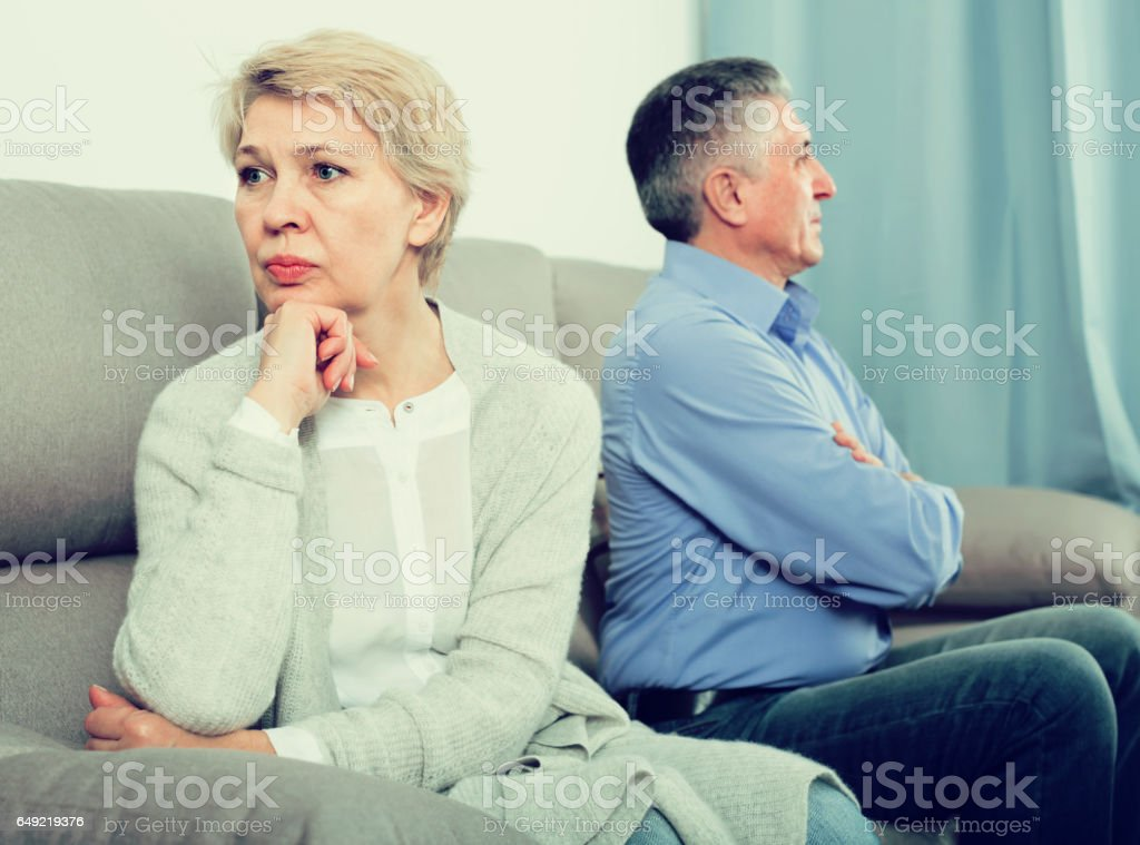 sad middle-aged couple quarreling at home with each other stock photo