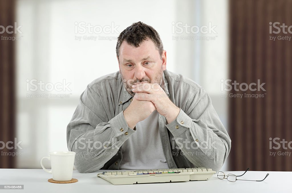 Sad middle-aged man sitting at white desk stock photo