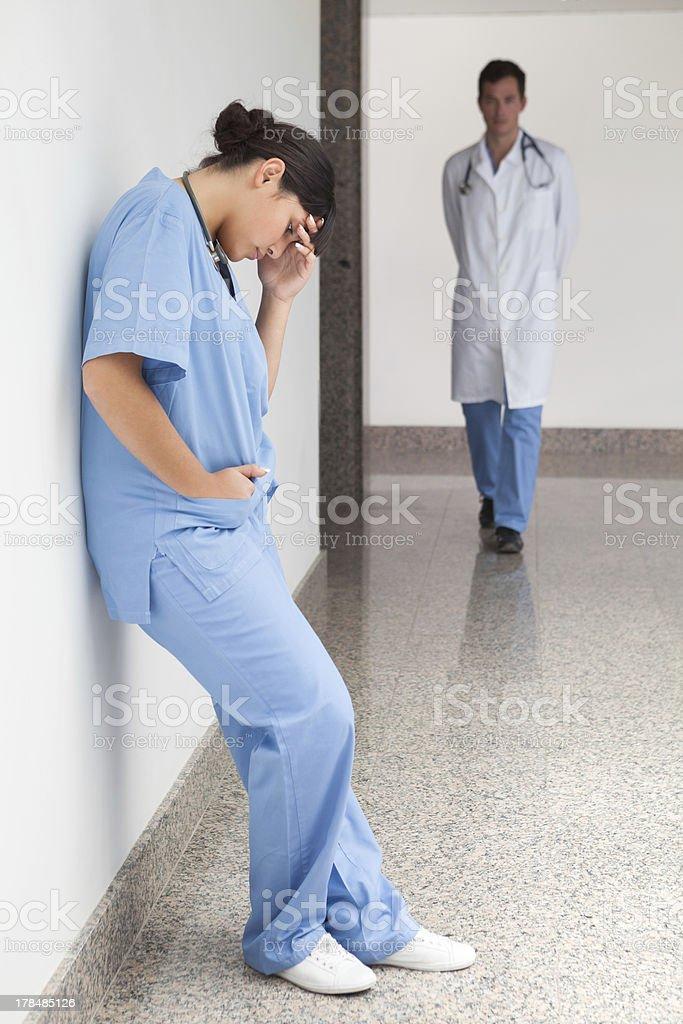 Sad nurse leans against wall royalty-free stock photo