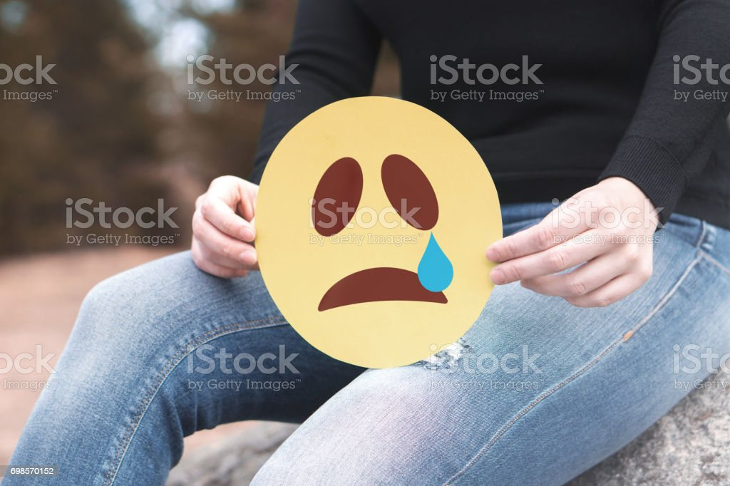 Sad paper emoticon in hand. Depressed woman holding printed crying smiley face and sitting on a rock. Modern   communication and smiley icon on cardboard. Sadness, depression and emotions concept. stock photo