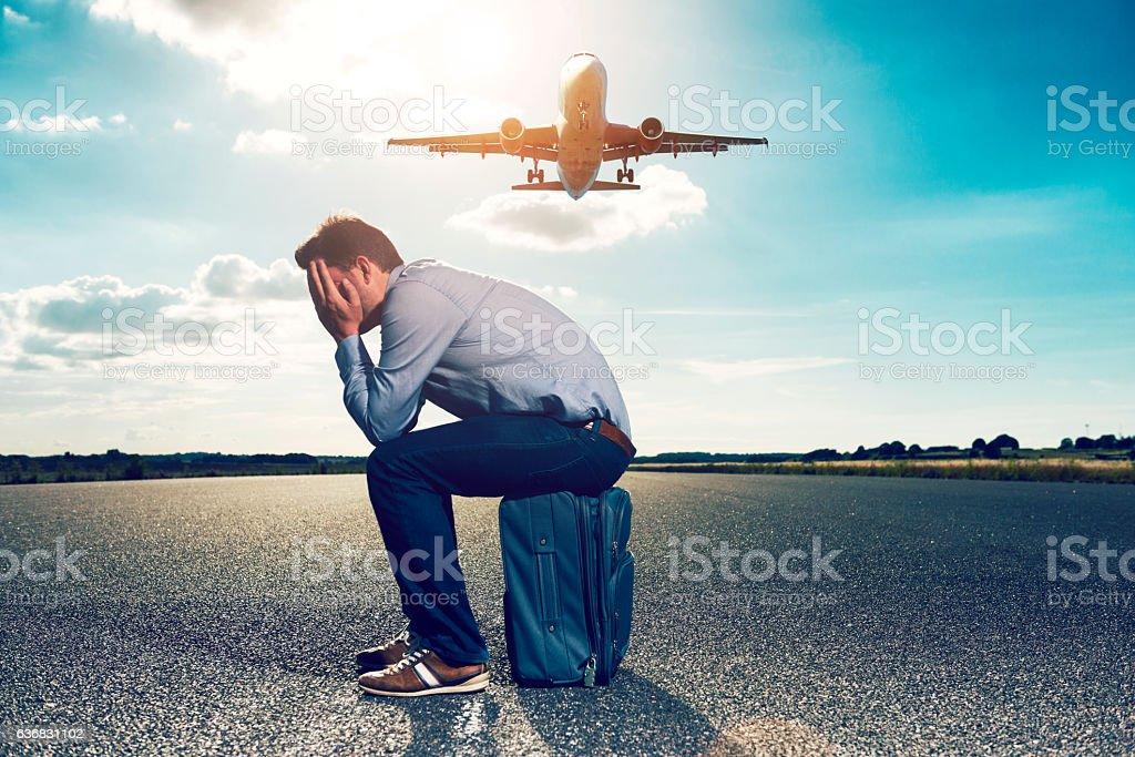 Sad passenger waits with suitcase for plane on runway stock photo