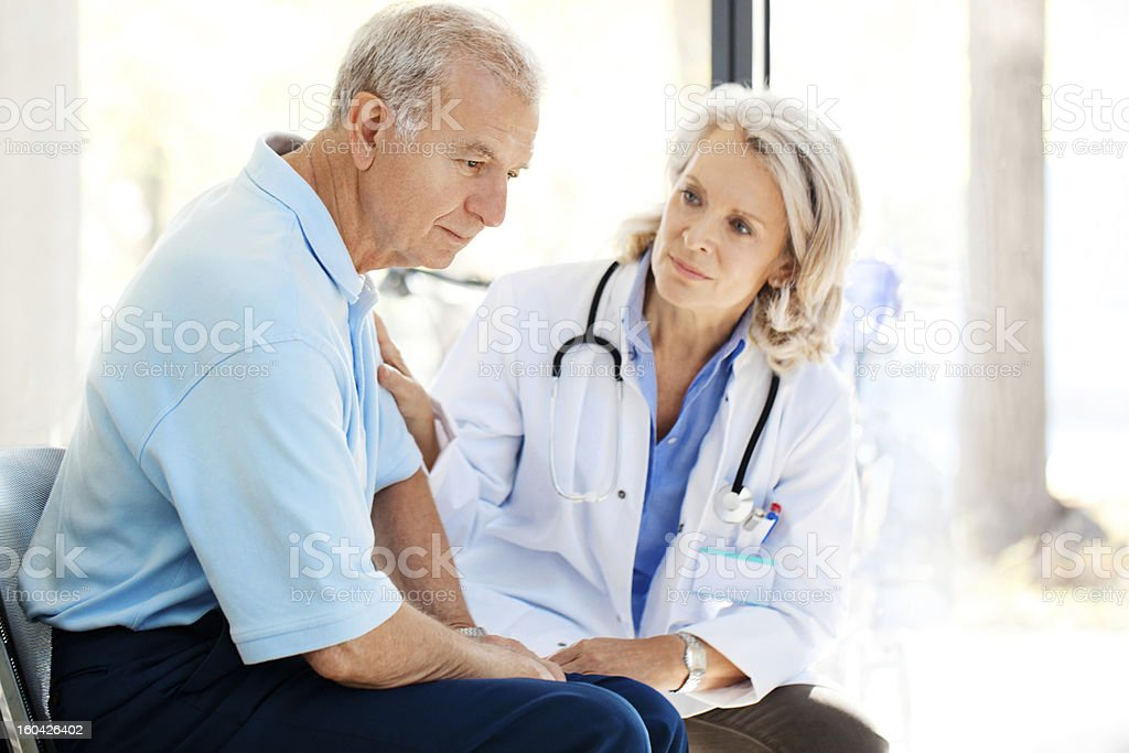 Sad patient being recomforted by a doctor stock photo