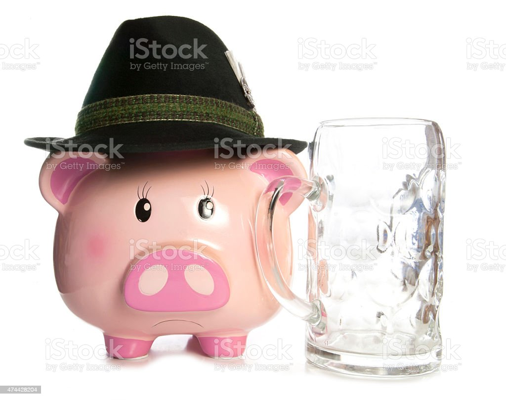 sad piggy bank wearing beer festival hat and empty pint stock photo