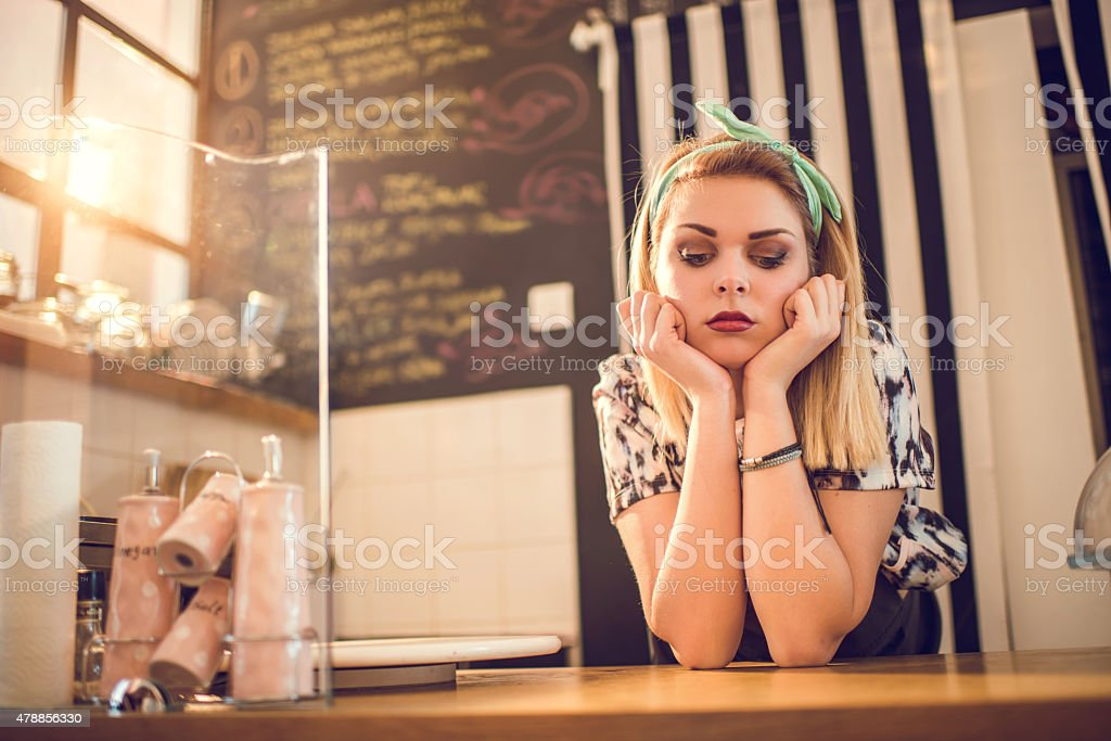 Sad retro styled female worker waiting for her customers. stock photo
