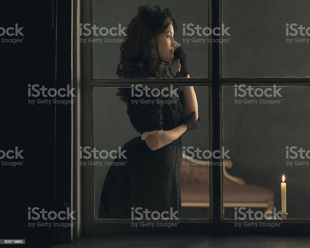 Sad retro victorian woman in black dress wiping tear. stock photo