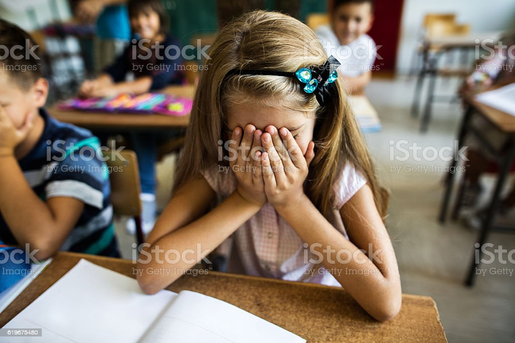Sad schoolgirl holding her head in hands in the classroom. stock photo
