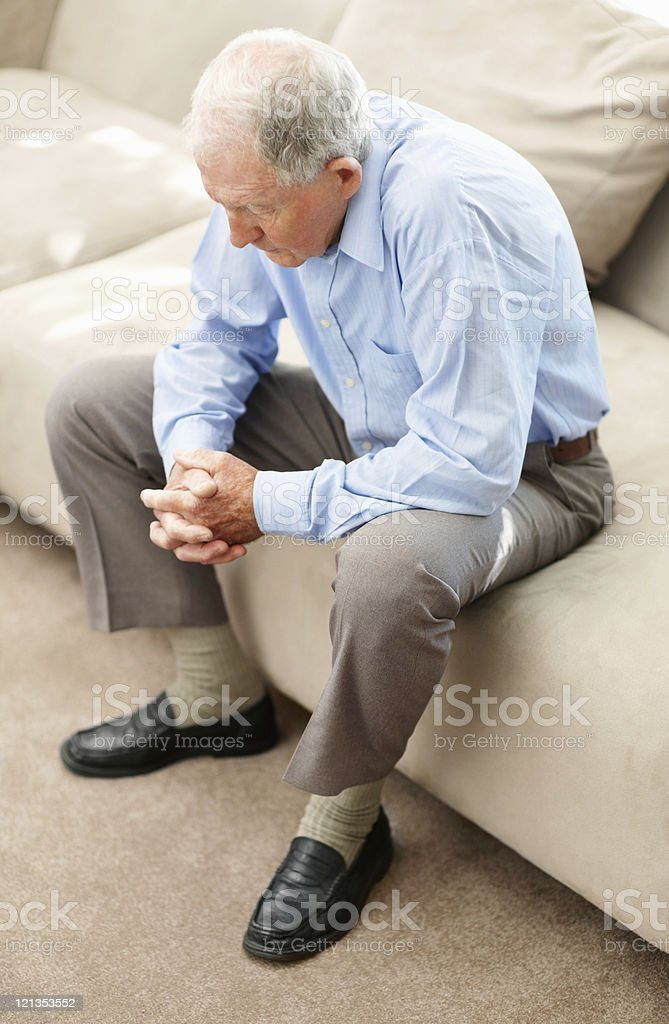 Sad senior man sitting on sofa royalty-free stock photo