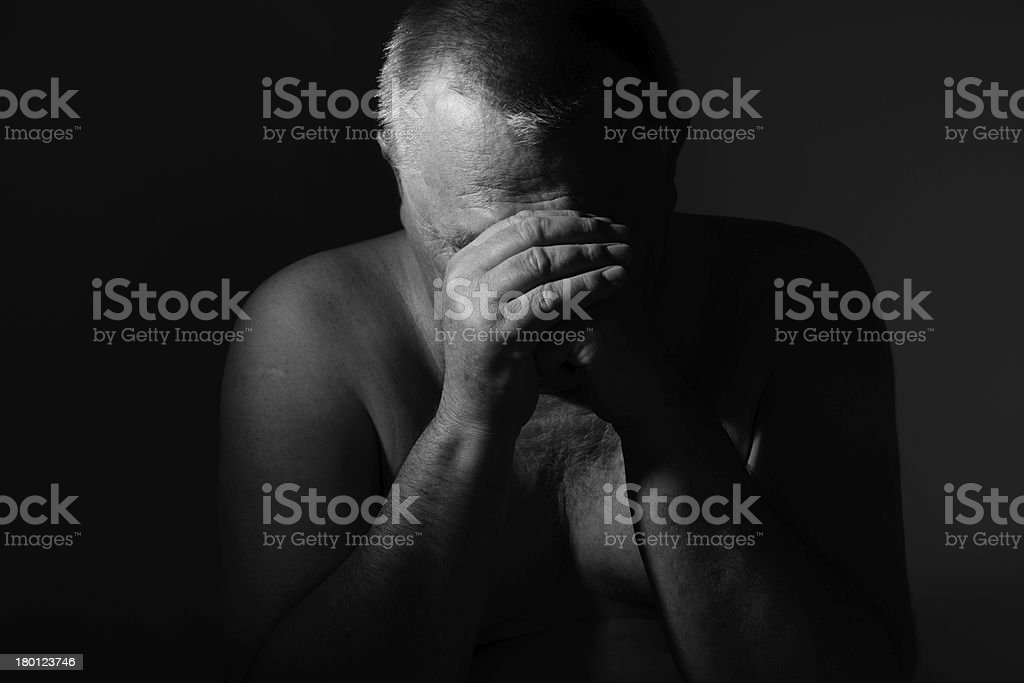 Sad senior man with hands on face over black stock photo