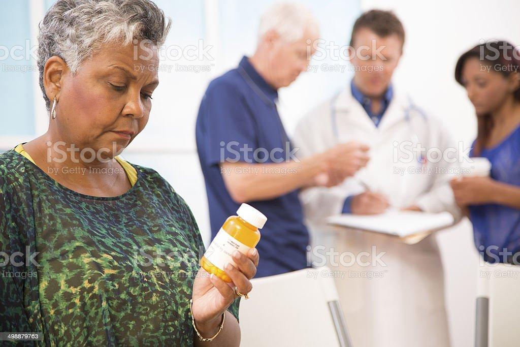 Sad senior woman abuses prescription medications. Doctor, patients background. stock photo