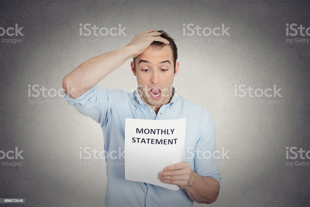 sad shocked funny looking young man disgusted at his corporate monthly statement stock photo