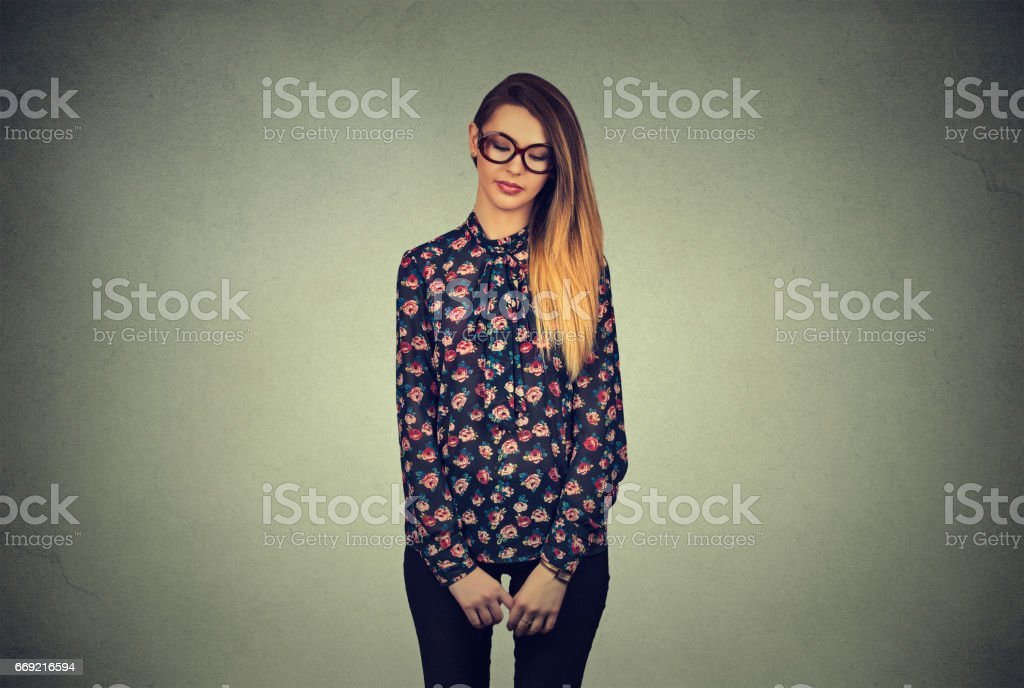 Sad shy insecure young woman in glasses looking down avoiding eye contact standing isolated on gray wall background stock photo