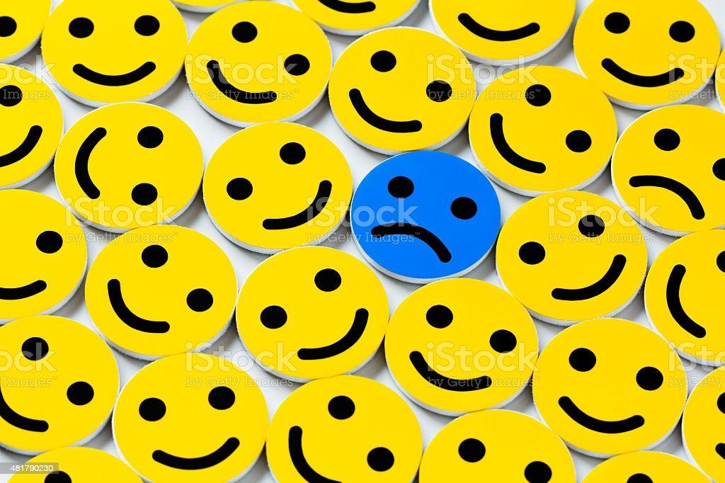 Sad smiley between happy ones stock photo