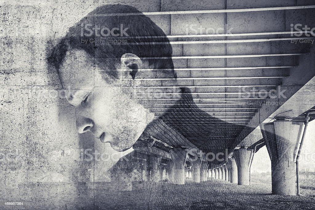 Sad stressed young man with concrete wall background stock photo