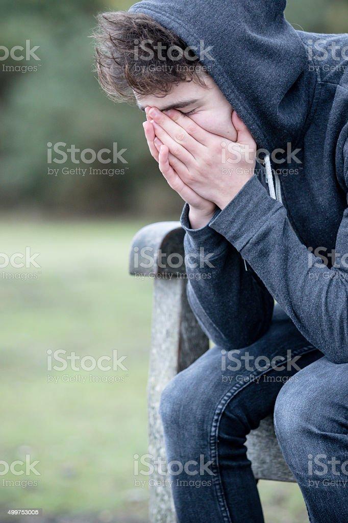 Sad Teenage Boy Sitting on A Bench stock photo