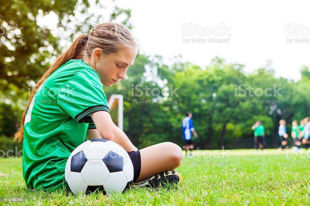 Sad teenage girl after soccer game stock photo