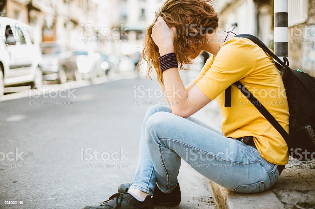 Sad teenage girl at the street stock photo