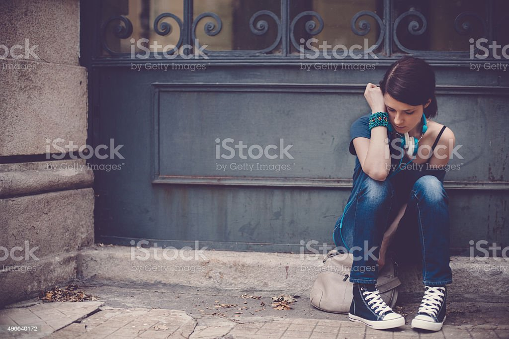 Sad teenage girl outside stock photo
