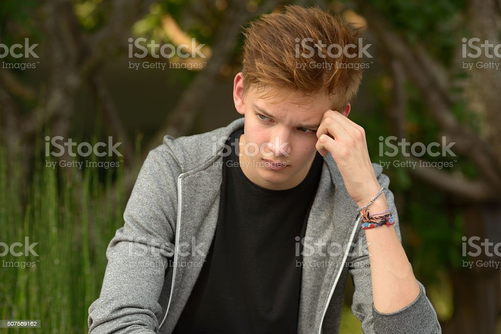 Sad teenager boy outdoors alone stock photo