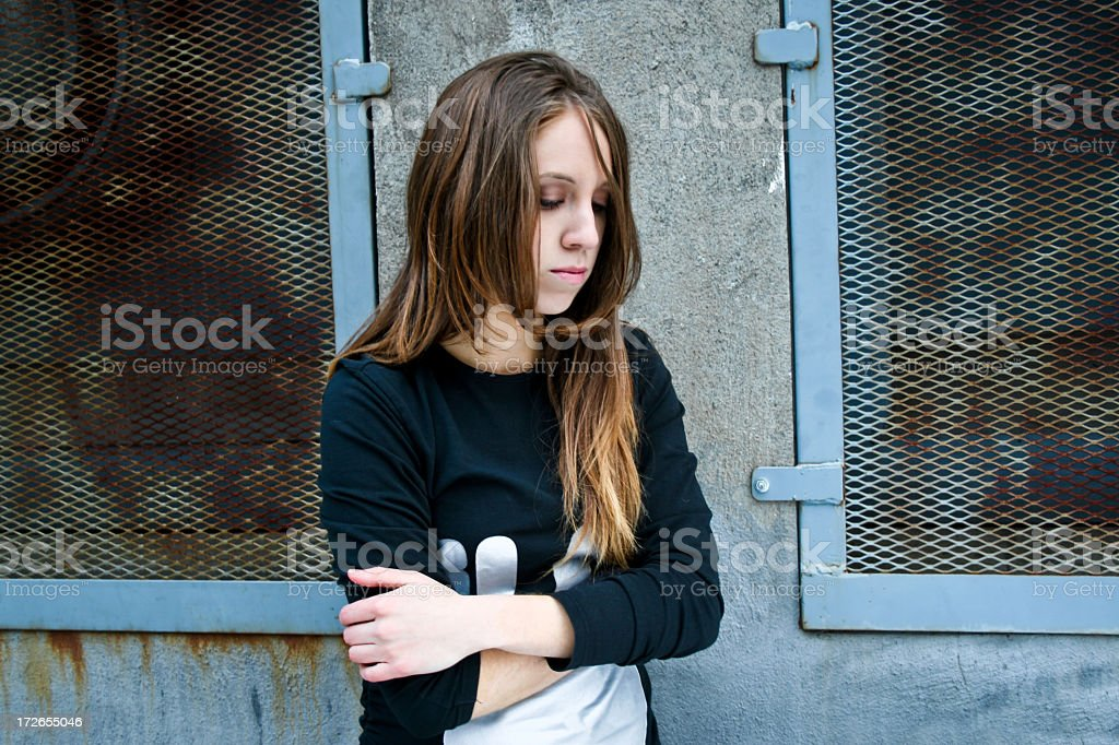 A sad teenager girl crossing her arms stock photo