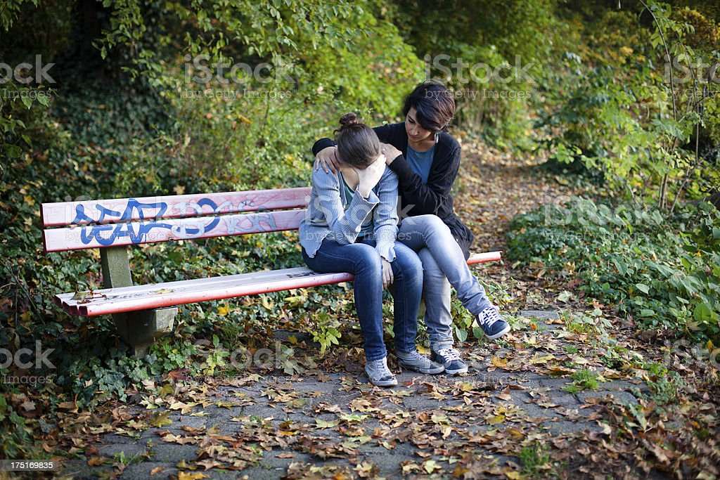 sad teenager girl is comforted by her female friend royalty-free stock photo