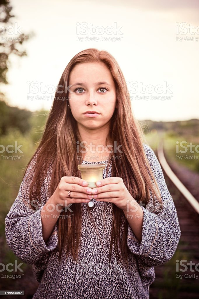 Sad teenager holds candle during a railroad track vigil stock photo