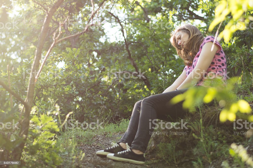 sad teenager sitting in the forest stock photo