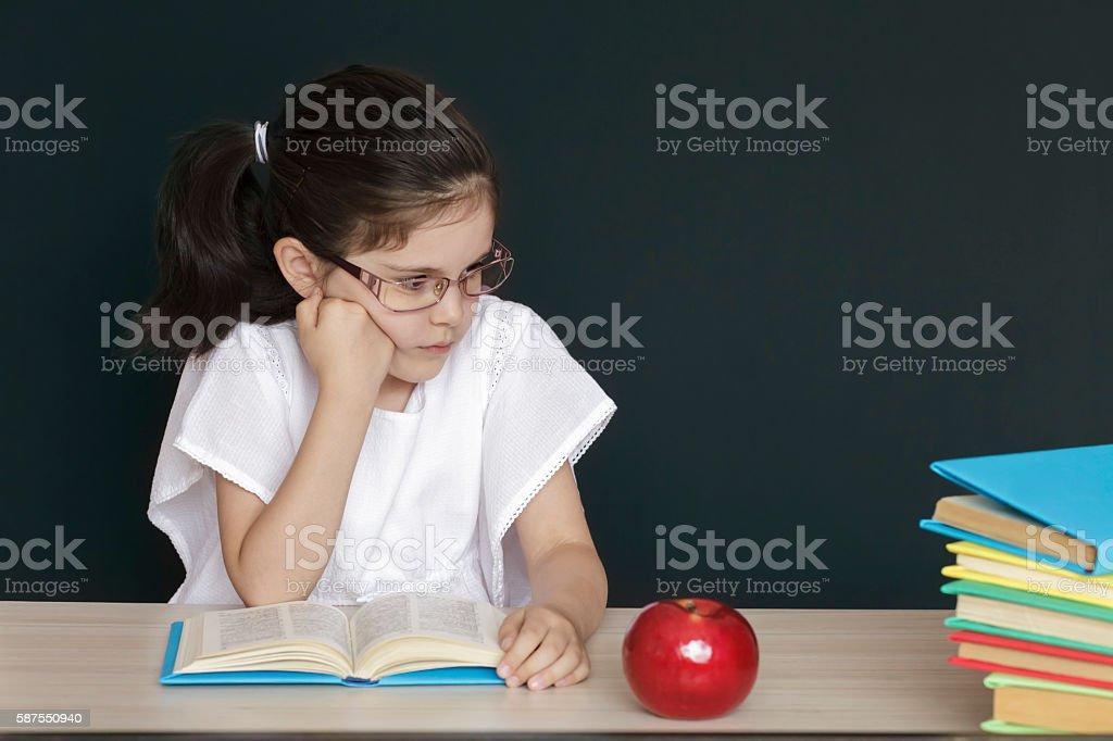 Worriedly schoolgirl in front of a black school board