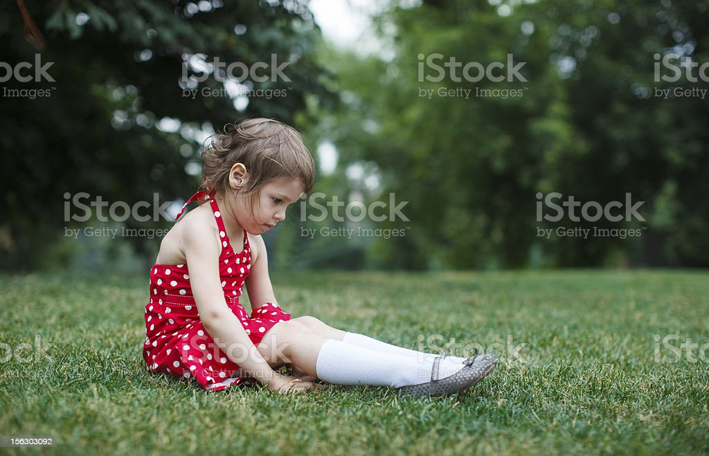 Sad toddler girl sitting on green grass royalty-free stock photo