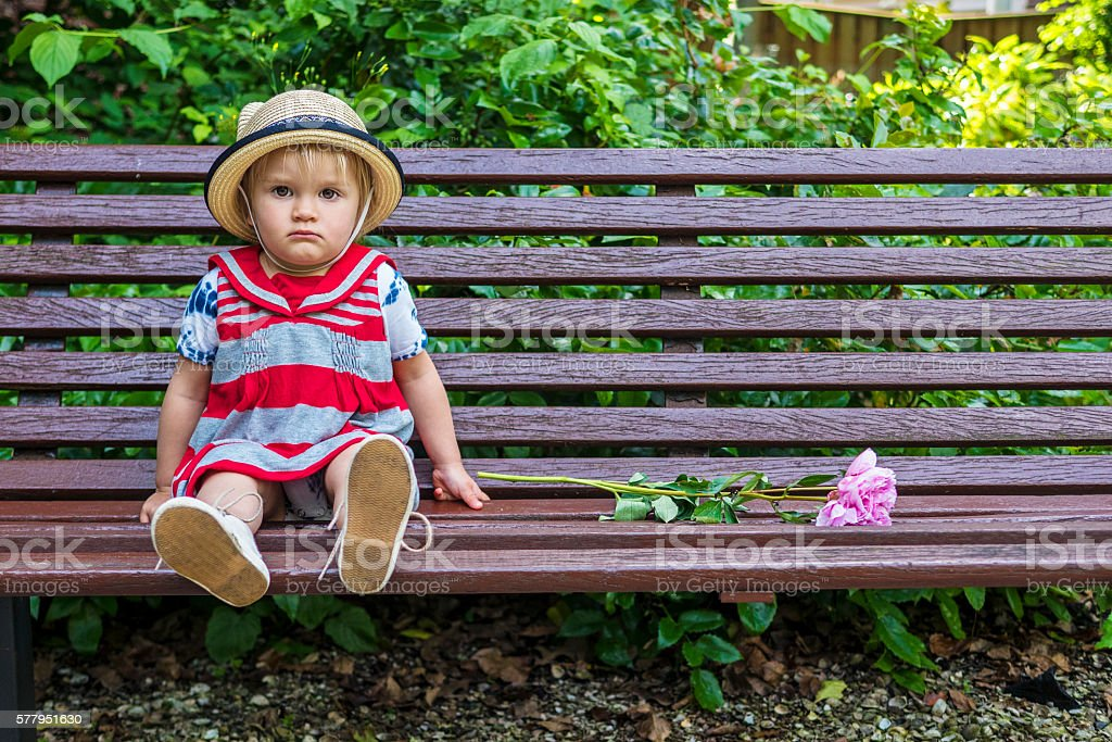 Sad toddler sitting on a bench stock photo