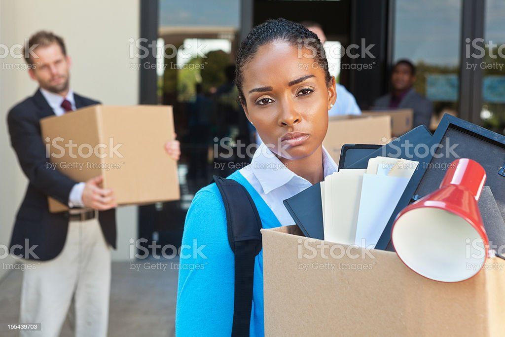 Sad unemployed woman leaving office after layoff or being fired royalty-free stock photo