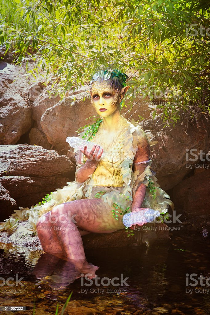 Sad water nymph holding plastic bottles in woods stream stock photo