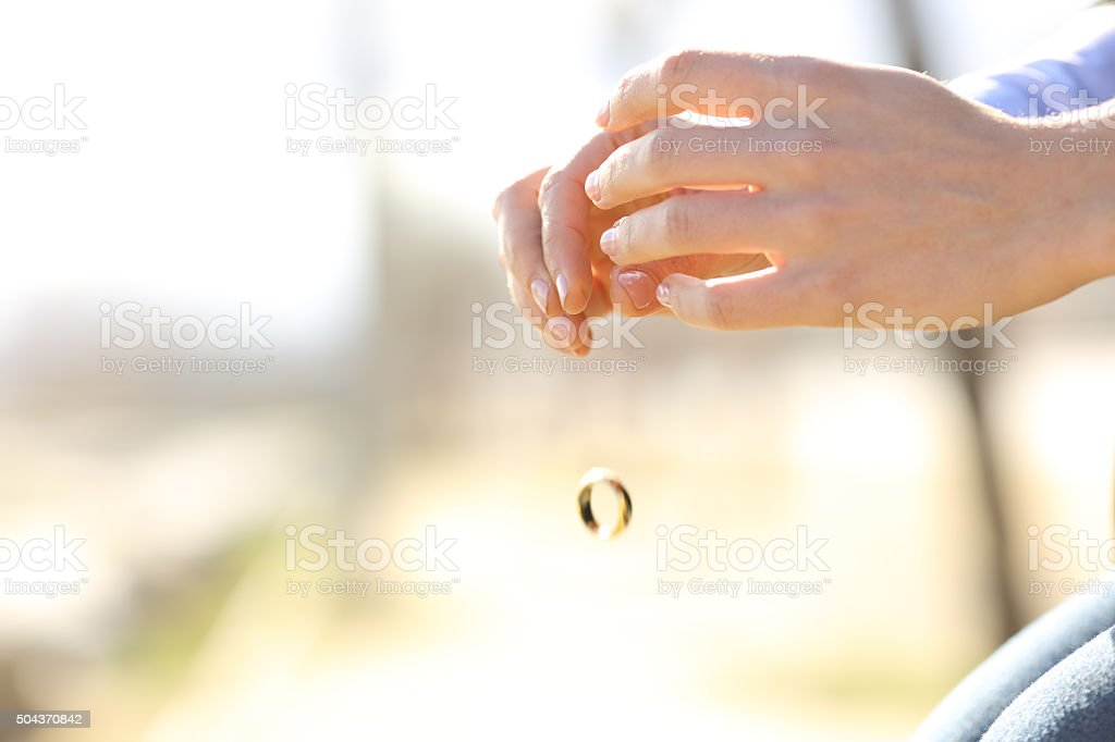 Sad wife hands dropping her wedding ring stock photo