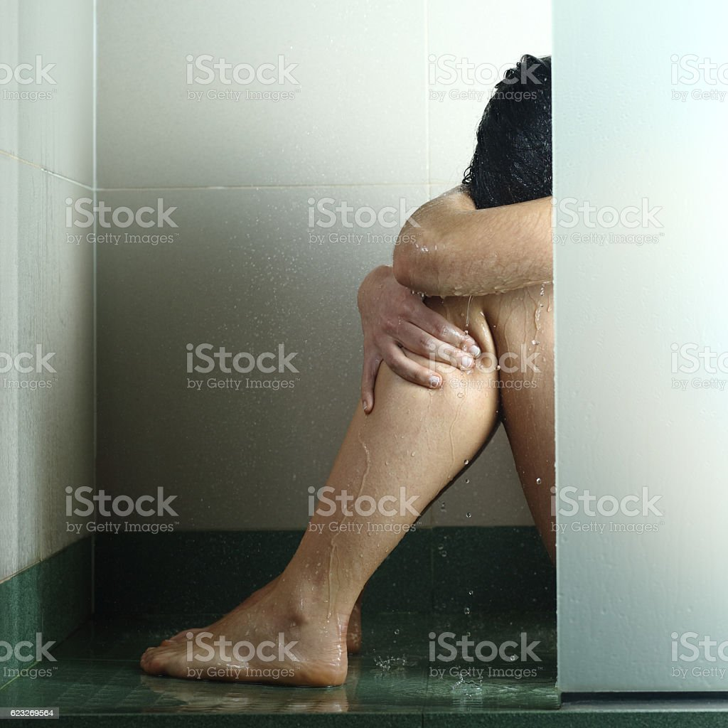 Sad woman after abuse in shower stock photo