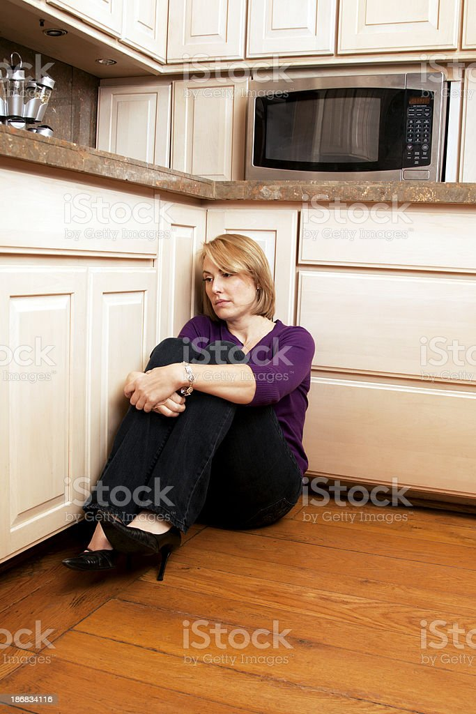 Sad Woman Against Kitchen Cabinets stock photo