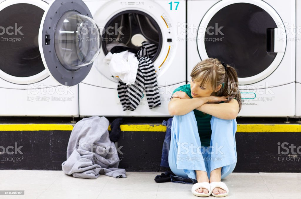 Sad woman doing laundry in laundromat royalty-free stock photo